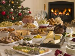 Table Filled With Boxing Day Buffet Lunch, Christmas Tree and Log Fire